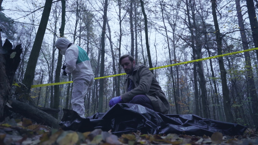 Detective looking at maniac victim body, forensic experts examining crime scene | Shutterstock HD Video #1041038138
