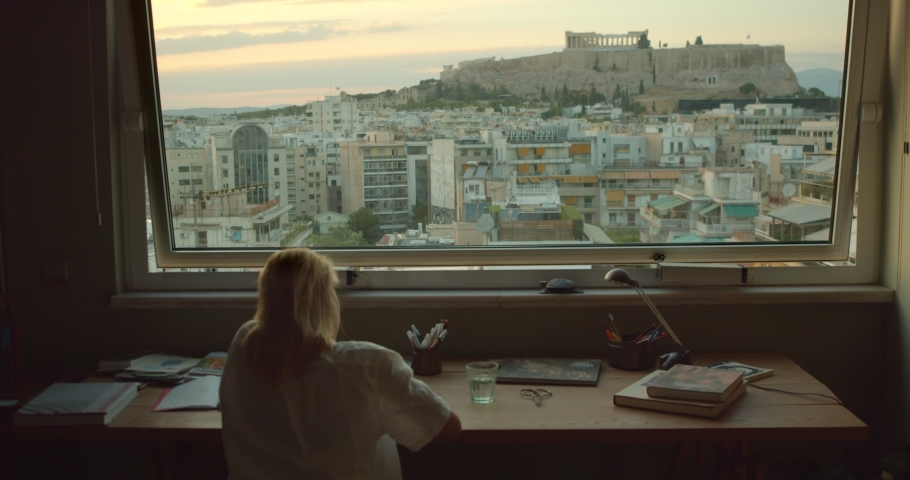 A girl in a casual sits in front of the city and writes | Shutterstock HD Video #1041068798