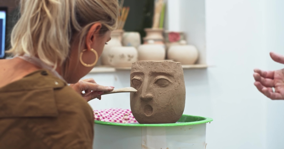 Two girls sculptors modeling clay face mask, online art education. Learning app. Creative Fun For Kids Arts, indoor home activities. Freelance alternative job experience, shoping craft market.   Shutterstock HD Video #1041084808