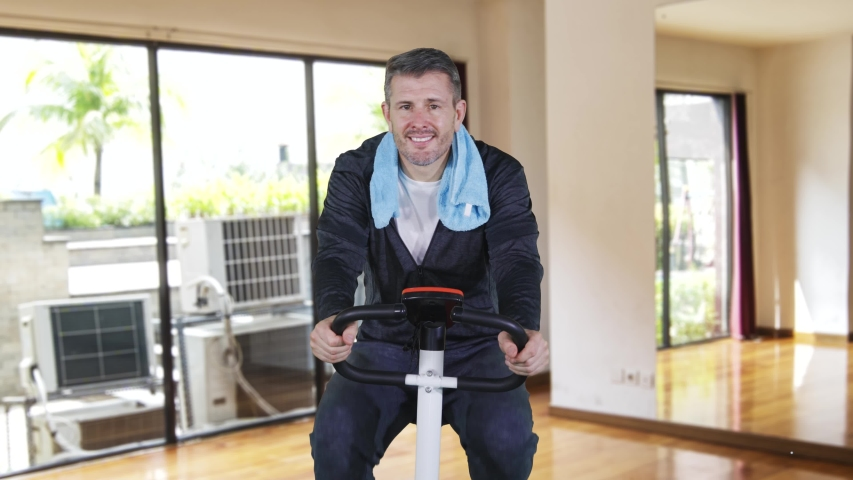 Mature man smiling at the camera while biking on an exercise bike. Shot in 4k resolution #1041118768