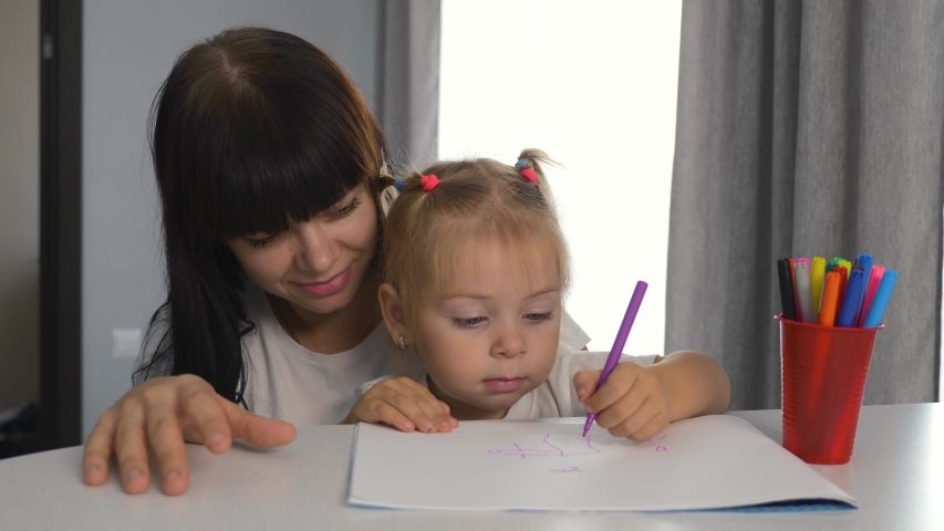 Happy family. Mom and daughter draw a picture in the album. Home schooling. Doing homework. Teamwork | Shutterstock HD Video #1041222058