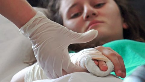 4k Doctor examining kid's broken hand. The patient with pain face in hospital bed. UHD stock footage