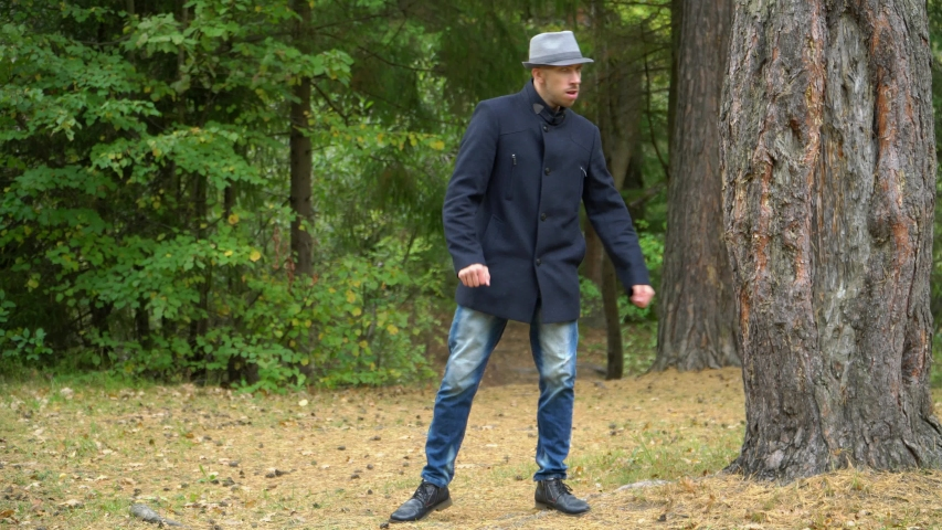 Business man in hat and coat in the woods happily dancing disco.   Shutterstock HD Video #1041457768