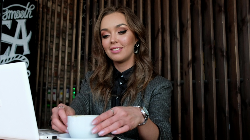 Beautiful business woman drinking coffee and working at laptop in a cafe. Girl buying in Internet and communicates in social networks.   Shutterstock HD Video #1041458518