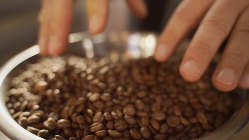 A man mixes different varieties of roasted coffee beans with his hands. Hands and coffee beans close-up.   Shutterstock HD Video #1041459448