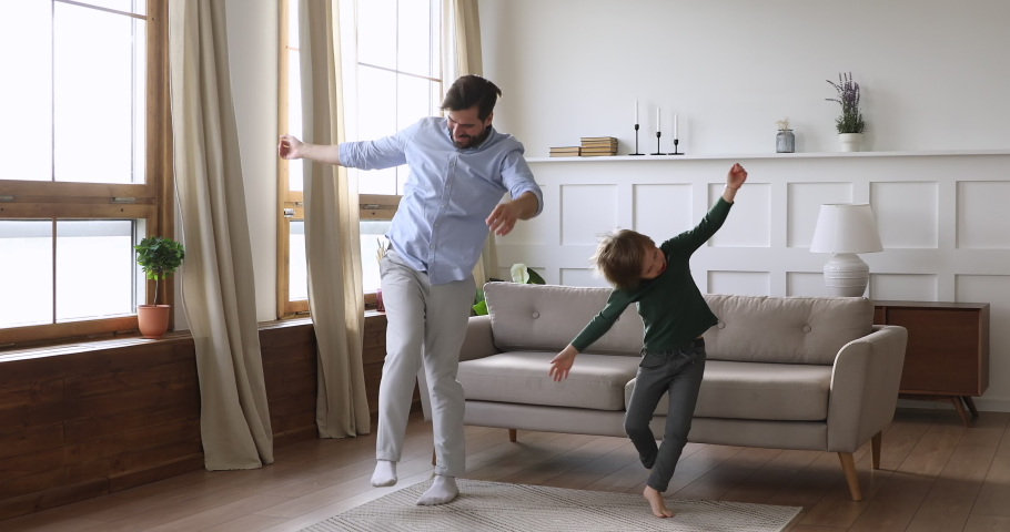 Playful crazy young daddy and cute kid son having fun dancing together in living room interior, happy funny active child boy copy father jumping laughing at home, carefree male family leisure indoors #1041538618
