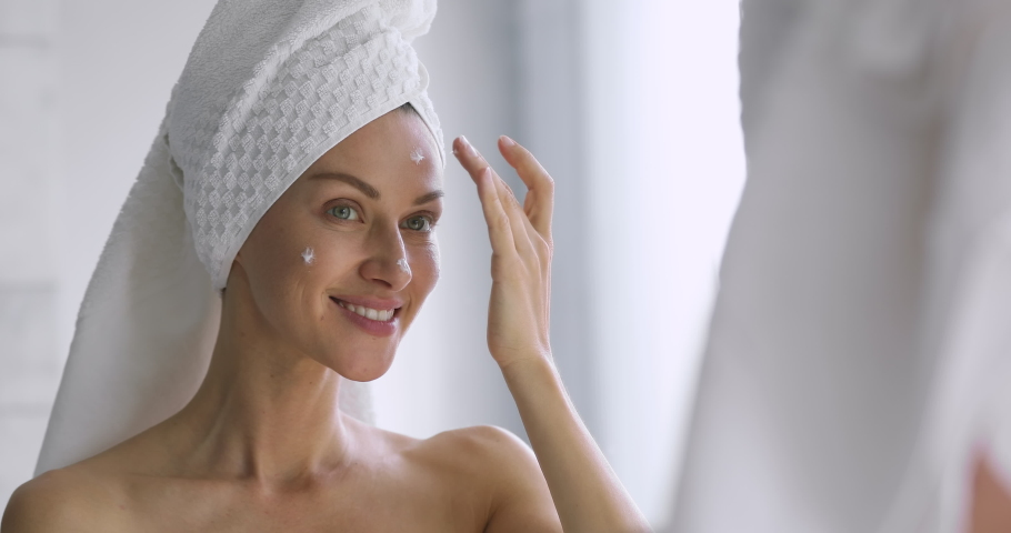 Funny happy attractive woman apply skincare cream on face look in bathroom mirror, healthy young lady wrap towel on head put moisturizing lifting facial creme, healthy skin care treatment concept | Shutterstock HD Video #1041547768