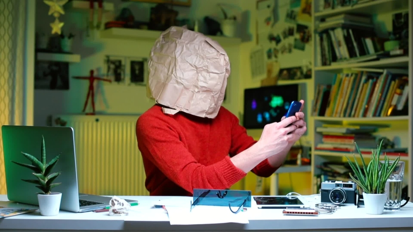 A businessman in red clothes with a paper bag on his head sits at a table in the office. Uses a mobile phone. Recognizes a new idea and calls a business partner.   Shutterstock HD Video #1041627718