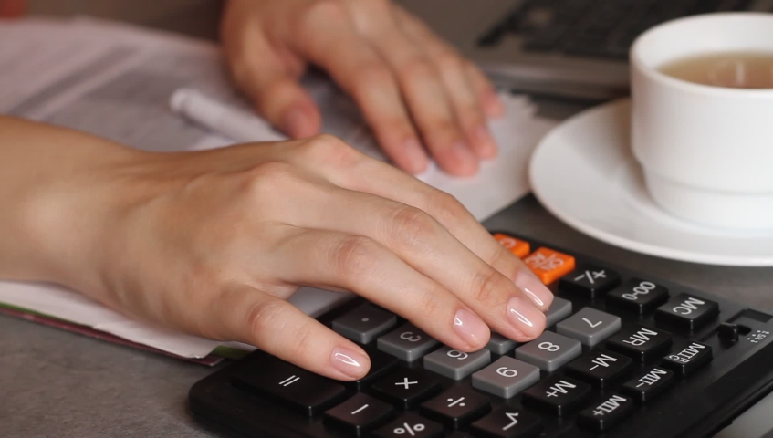 Close up of female accountant or banker making calculations. Home finances, investment, economy, saving money or insurance concept. Hands closeup. | Shutterstock HD Video #1041684388