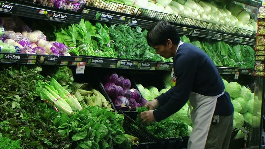 Worker facing produce display of fresh leaf lettuce in grocery store.