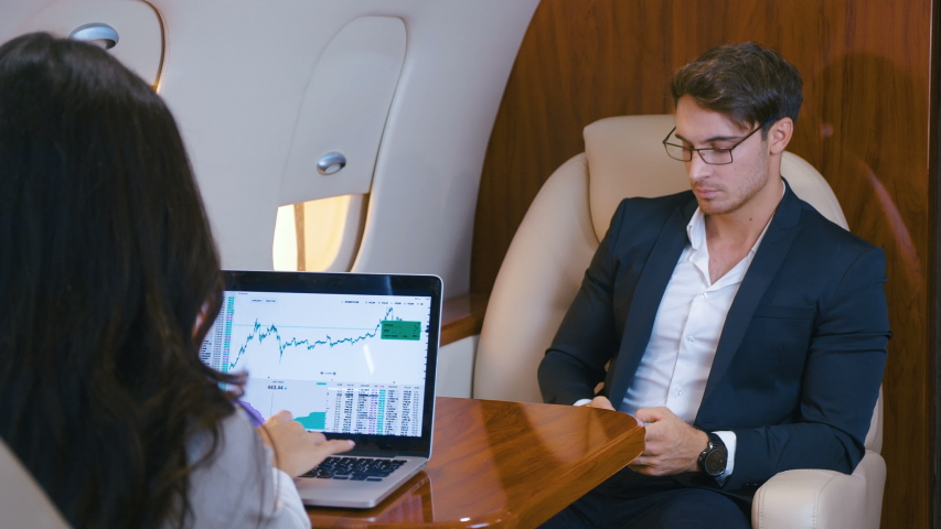 Successful business people fly a private jet. Working at laptop. Using a smartphone. Businessman and businesswoman flying in the first class of an airplane.   Shutterstock HD Video #1042265008