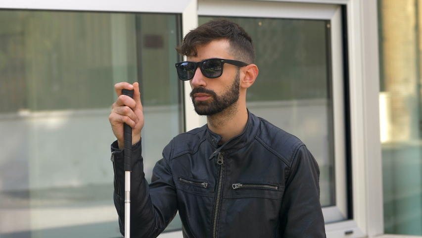 Blind young man using smartphone in the city.technology,handicap, help   Shutterstock HD Video #1042273468