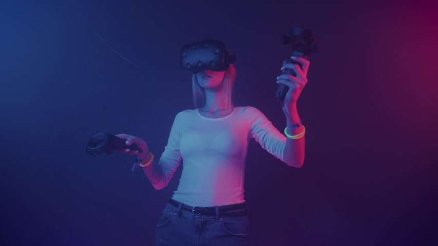 Young Girl Gamer Wearing Virtual Reality Glasses Playing Game Holding and Moving Joystick Controllers Standing at Neon Lights Background Virtual reality Entertaiment Concept | Shutterstock HD Video #1042277218
