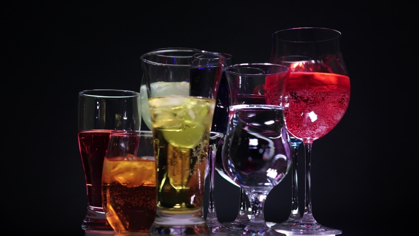 Liquor in the glass. Many shaped glasses with color cocktails and drinks. Classy bar at night club concept. Nightclub live style. New Year or Christmas celebration.   Shutterstock HD Video #1042284178
