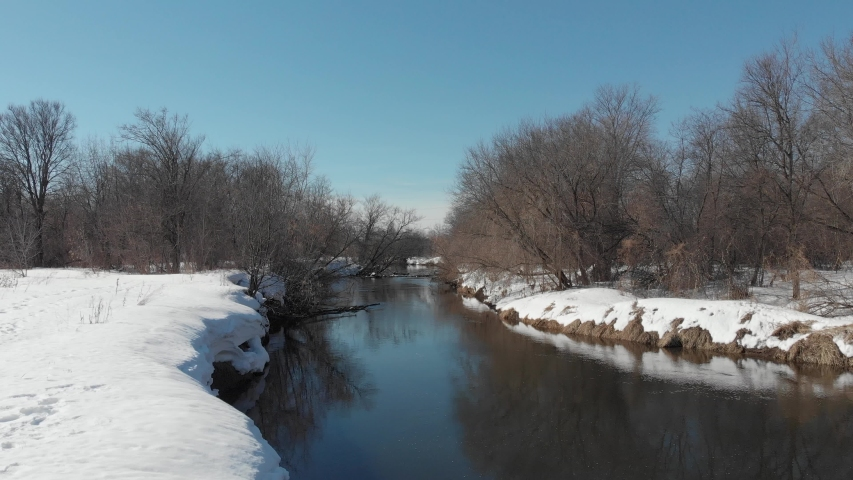 View from the quadrocopter on the river in spring. The river flows among white snow and bare trees | Shutterstock HD Video #1042372708