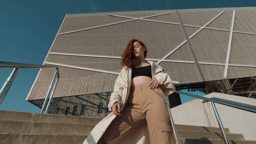 Young Red-Haired Girl On The Street. Girl Has Long Curly Hair. Urban Fashion Concept. Girl Stands On The Stairs Near Modern Building. | Shutterstock HD Video #1042425238