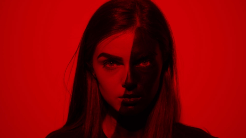 Face attractive young woman half face girl drawn in black look at camera serious red light background flashing colored light abstract art beauty artistic creative decoration design fashion slow motion | Shutterstock HD Video #1042456198