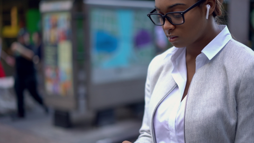 Black female entrepreneur standing at New York urbanity and using cellphone device for communicate with partners, business woman in electronic earbuds searching audio message for listen  | Shutterstock HD Video #1042487938