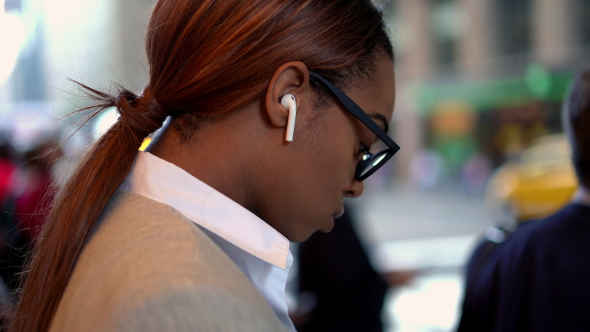 Young dark skinned woman in classic glasses doing crosswalk in city downtown using cellphone device for communicate on way, female in earbuds writing text email connected to 4g wireless  | Shutterstock HD Video #1042487968