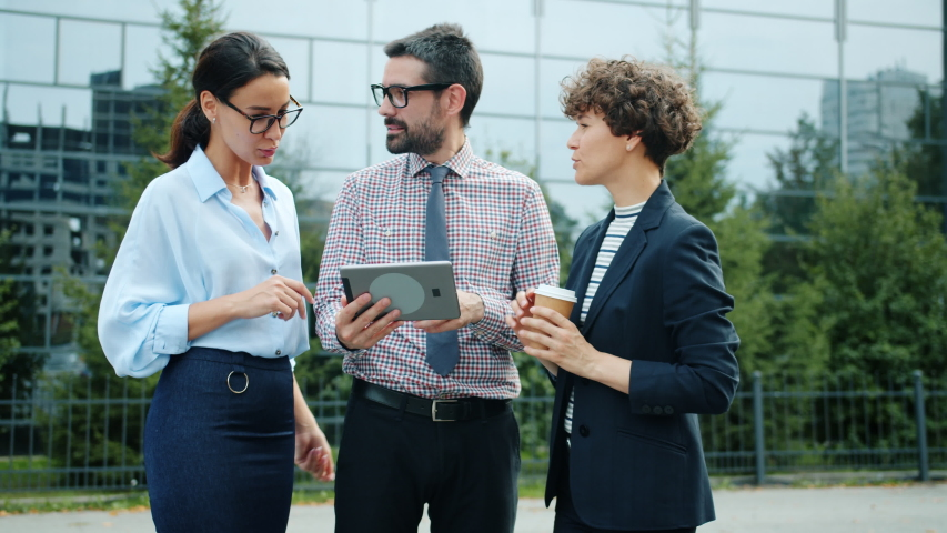 Group of male and female coworkers young people are looking at tablet screen talking outside business center in city. Modern technology and communication concept. | Shutterstock HD Video #1042493098