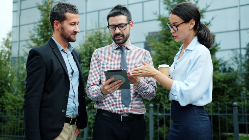 Slow motion of male and female colleagues talking and using tablet outside in city busy with discussion about work. People and communication concept. | Shutterstock HD Video #1042493158