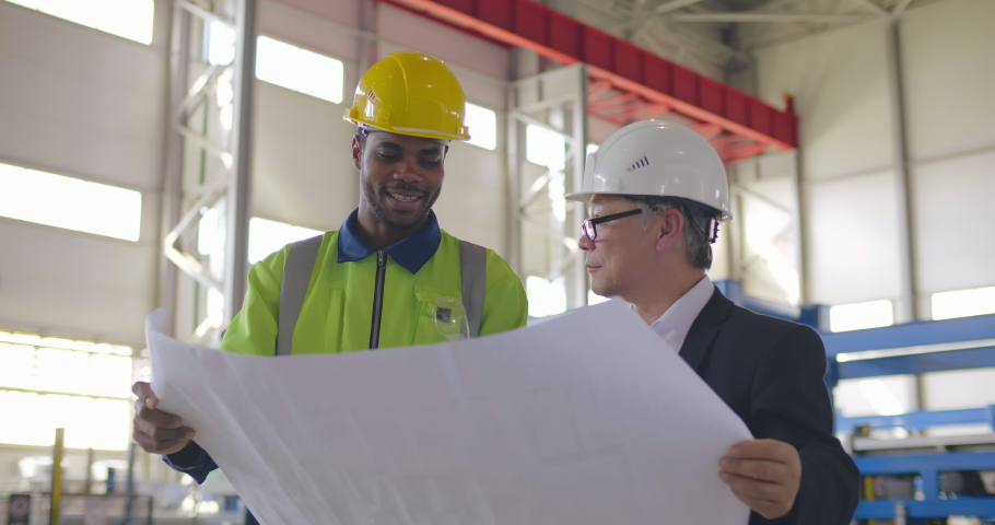 Team of workers at heavy industry enterprise discuss layout in blueprint. Asian engineer and black factory worker communicate about drawing on industrial background | Shutterstock HD Video #1042494778