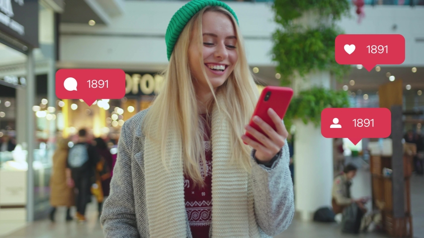 NEW YORK - April 5, 2019: Portrait smiling young woman use phone in shop mall typing social media icons with like comment follower counter quick increase blogger influencer adult communication slow | Shutterstock HD Video #1042499488