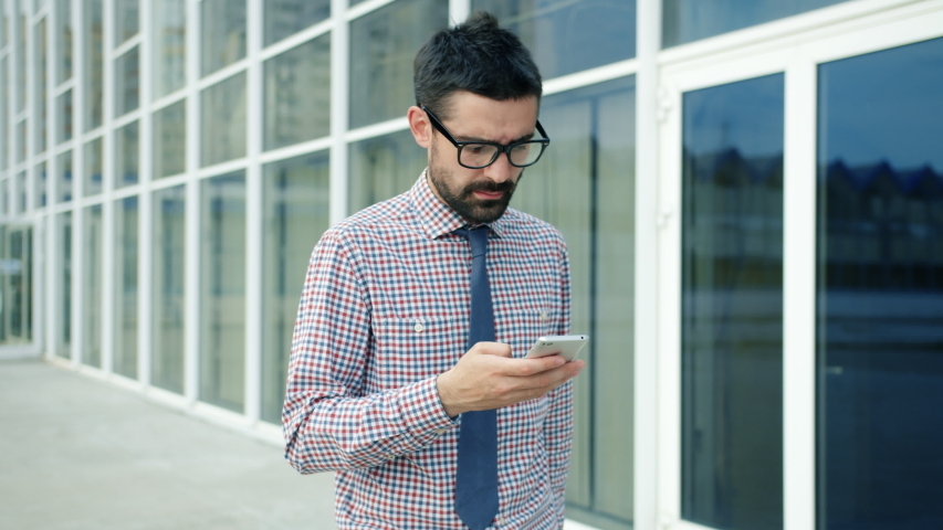 Serious banker using smartphone outdoors walking in business district alone communicating with clients busy with device. People, youth and city lifestyle concept. | Shutterstock HD Video #1042558168