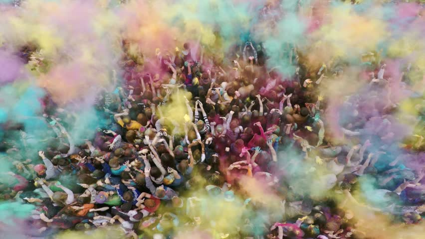Aerial flight above dancing crowd on Holi Festival Of Colors. Crowd of people colored powder and having fun. Russia, Chelyabinsk, 13 June 2015