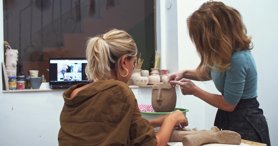 Beautiful red and blonde female artist using raw clay material creating human face on ceramic pot vase in craft studio with working laptop computer on background. Freelance. Handmade art business. | Shutterstock HD Video #1042593388