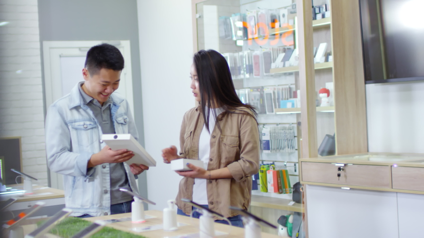 Handheld shot of young Asian couple shopping at gadget store, holding boxes with purchases and talking | Shutterstock HD Video #1042603108
