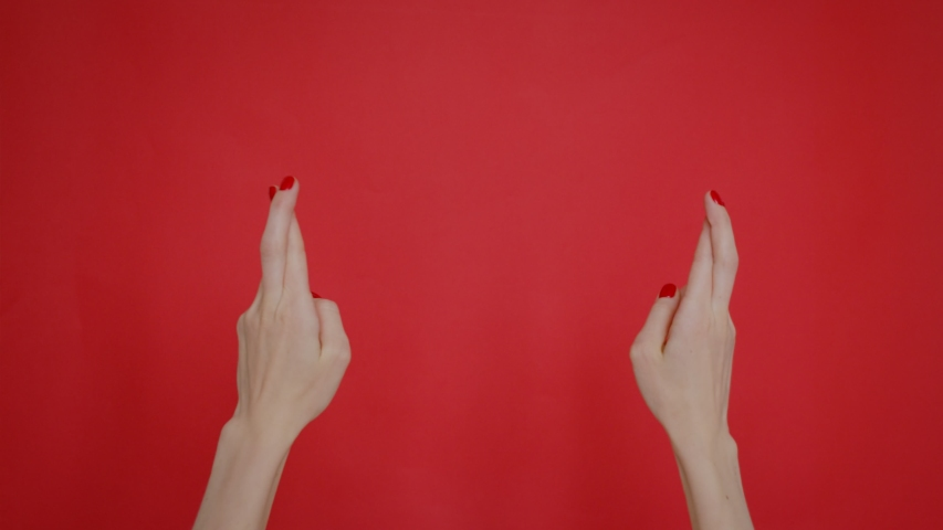 Woman hands keeping fingers crossed, making wish isolated over pastel red background in studio. Copy space for advertisement. With place text or image promotional content. | Shutterstock HD Video #1042723618