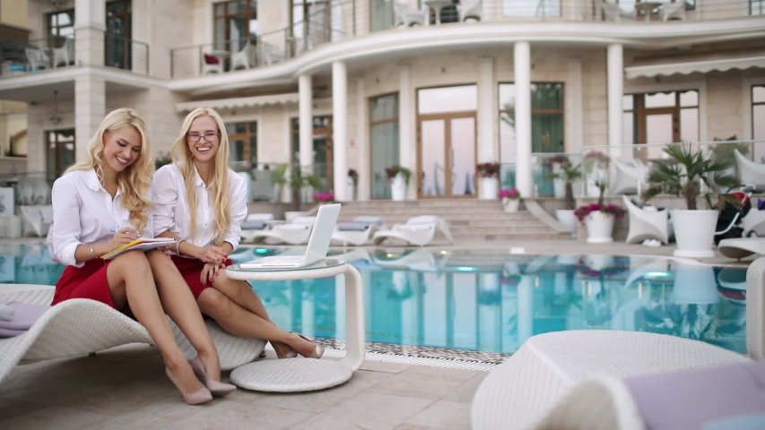 Summertime hotel business. Smiling blonde businesswomen twins in white blouses and red skirts  communicate typing on a laptop and talking to each other, hotel facade with large pool on the background.   Shutterstock HD Video #1042793218