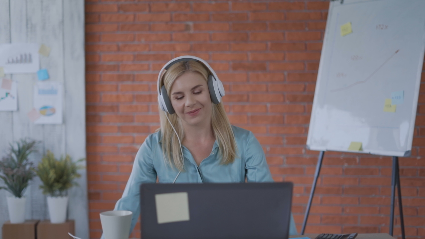Cheerful cheerful girl listens to music in the office for the first lunch break. 4k