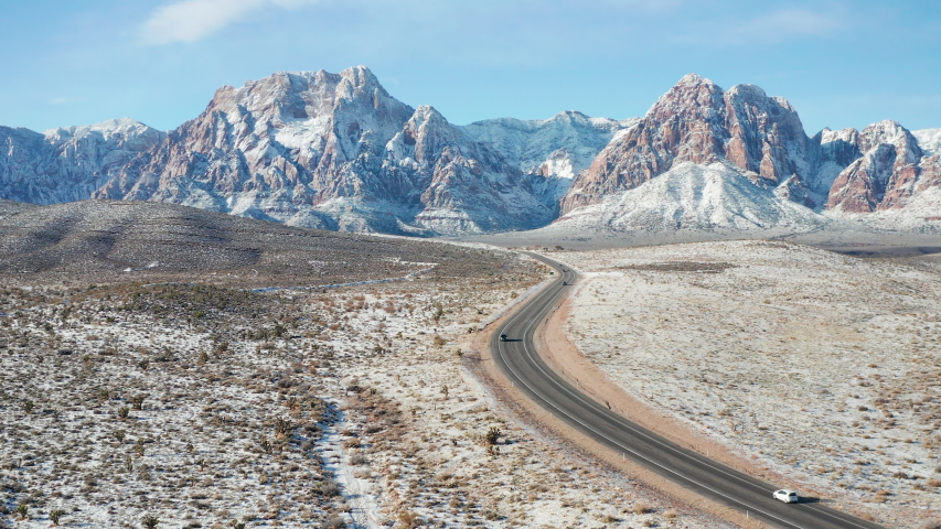 Aerial shot of cars driving in snow desert mountain landscape in Red Rock Canyon | Shutterstock HD Video #1043706718