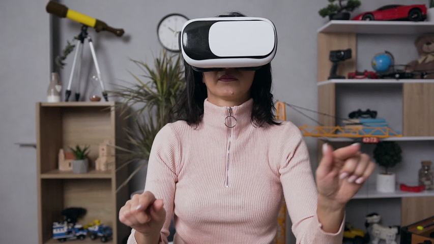 Slow motion of pleasant concentrated 35-aged woman which using augmented reality glasses, working on virtual computer | Shutterstock HD Video #1044511258