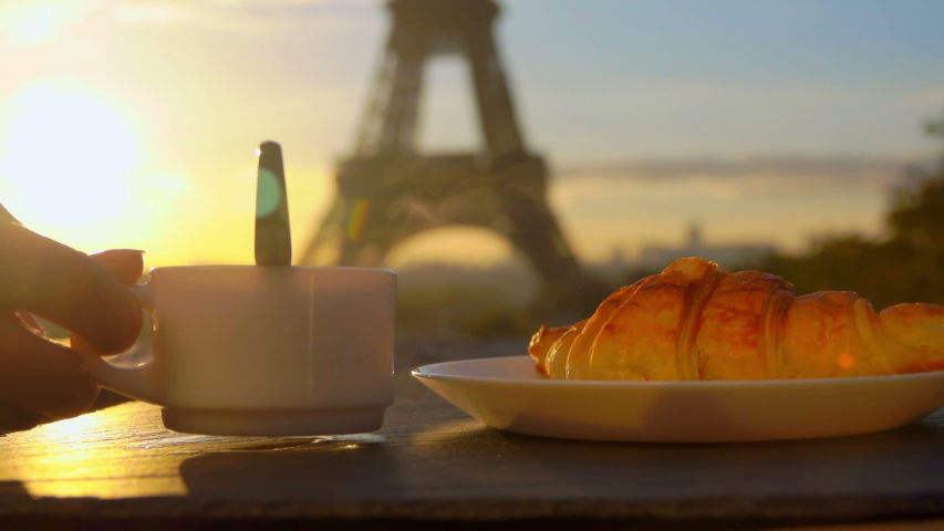 Cup of morning coffee with freshly baked croissant on the background of the Eiffel Tower, Paris, France | Shutterstock HD Video #1044717448
