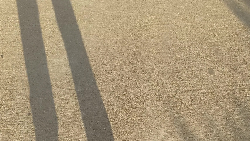 Man is walking along the road. Shadow of the legs against the sunset. Camera is looking down. Abstract Concept of improve, success, effort | Shutterstock HD Video #1044754138