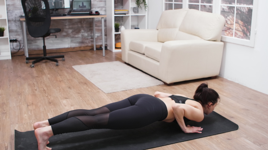 Attractive woman in leggings stretching her back on yoga mat. | Shutterstock HD Video #1044780178