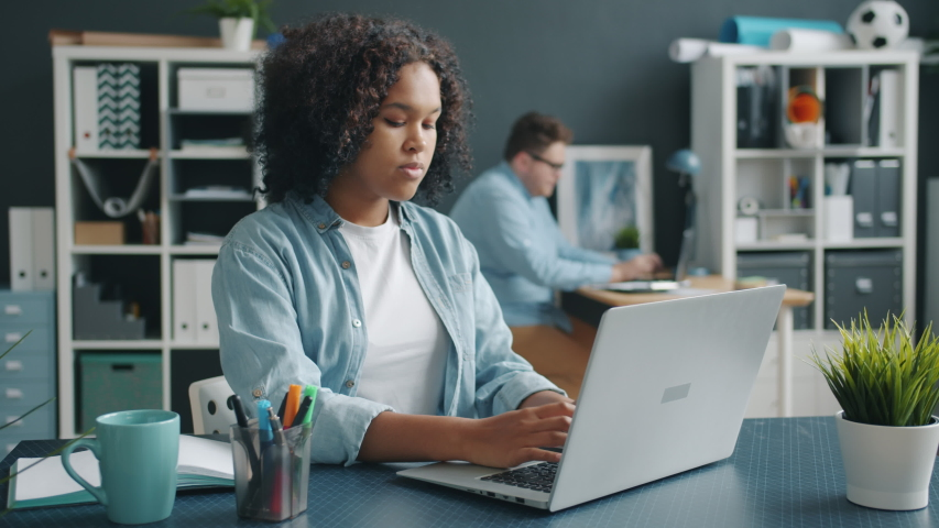 Beautiful Afro-American girl is working with laptop in office then talking to male colleague coworking unsing modern technology. People and communication concept.   Shutterstock HD Video #1044817348