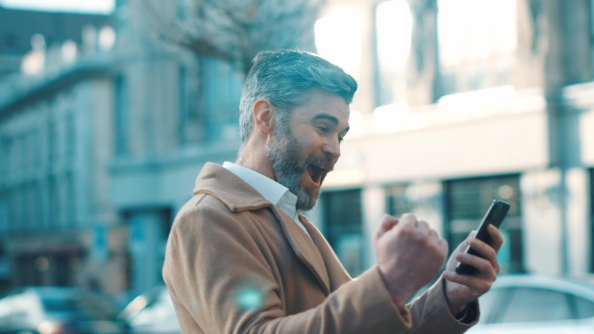 Happy successful middle aged businessman walks along the street looks around and uses phone good news win texting message works feels happy emotions outdoor business tehnology close up slow motion   Shutterstock HD Video #1044823618