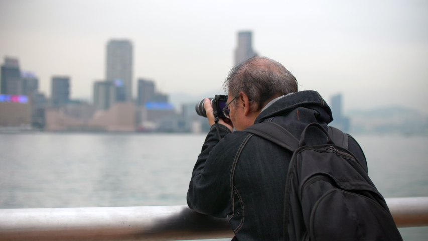 Man Takes Photos of Boats on Victoria Harbour From Hong Kong Pier Daytime 4k   Shutterstock HD Video #1044868078