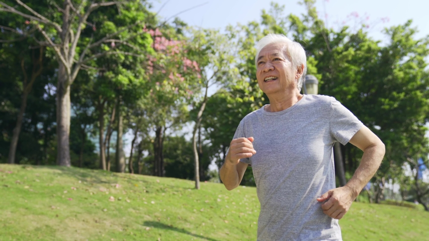 Happy asian old man jogging outdoors in a park   Shutterstock HD Video #1044871738