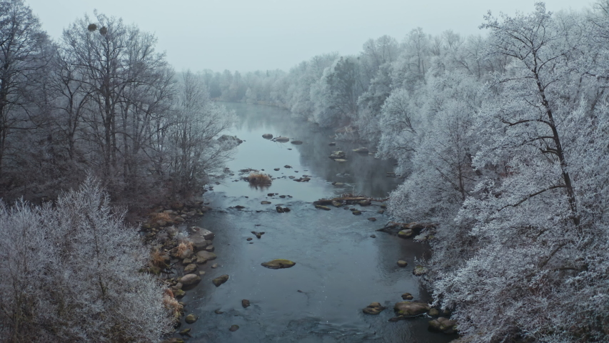 Drone flight over the river in winter. Beautiful nature landscape of the long river and white trees at both sides. | Shutterstock HD Video #1044901858