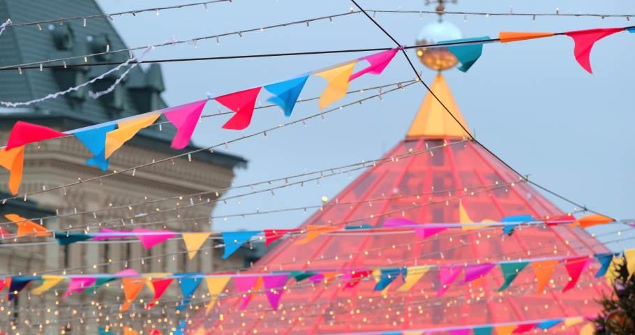 Many small colorful flags and electric garlands swaying in the wind  decorating the city. Holiday decorations. Festive abstract background. 4K slow motion footage | Shutterstock HD Video #1044925708