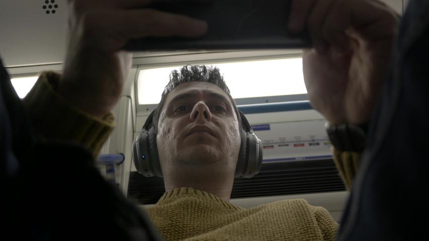 Below upward shot of man oning train using his cell phone watching aie | Shutterstock HD Video #1044937888