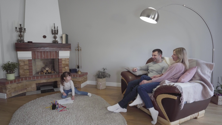 Little brunette Caucasian girl sitting on floor and drawing as her parents sitting on armchair. Pretty daughter coming to father and mother and hugging them. Young family resting together indoors. | Shutterstock HD Video #1045000978