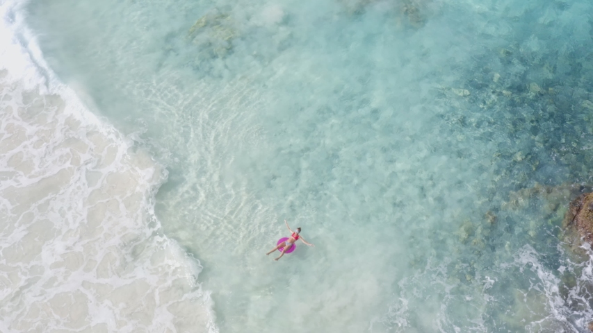 Drone aerial view of young woman floating on inflatable pink ring over turquoise waters enjoying sunbathing and vacations in tropical destination. People travel tourism holidays concept | Shutterstock HD Video #1045038208