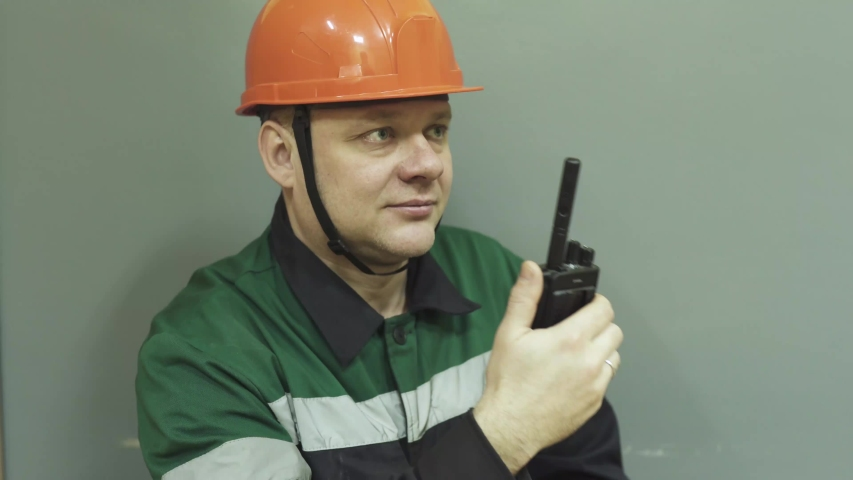 The face of a man in a work uniform of an engineer at work. The engineer speaks on the radio, puts on a helmet, glasses, and turns on a flashlight.  | Shutterstock HD Video #1045091578