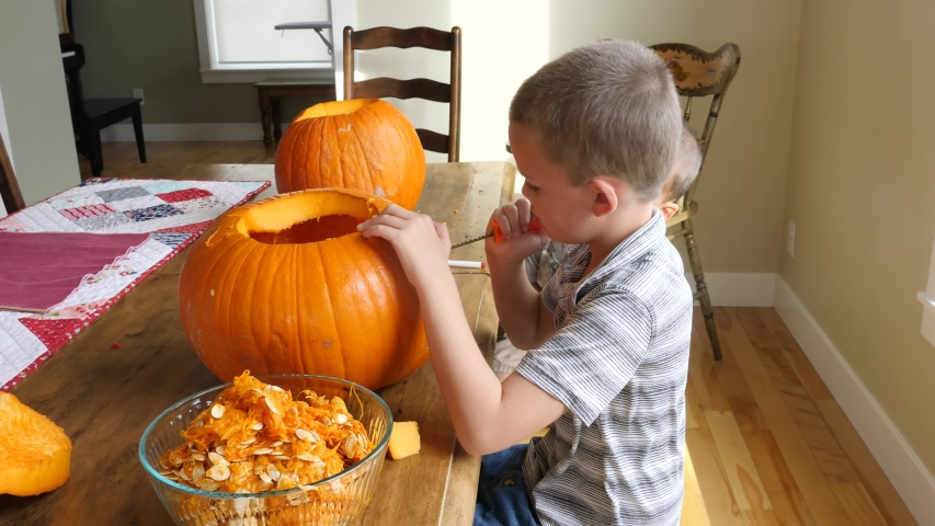 A family carving pumpkins for halloween at the kitchen table in their house | Shutterstock HD Video #1045115368